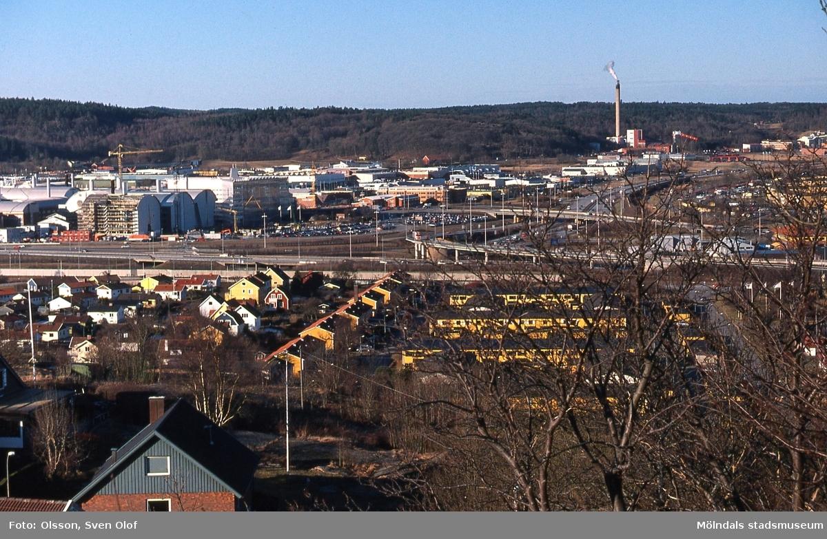 Vy från öster över bostadsbebyggelse i Brännås mot Åbro industriområde i Kärra, Mölndal, år 2002. I bakgrunden till höger ses även Riskullaverket. FD 12:39.