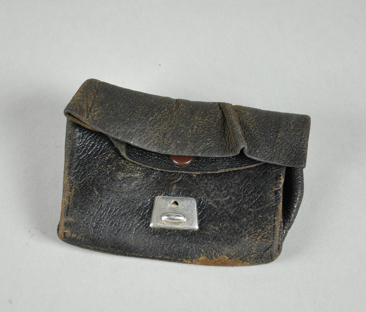 Lommebok av skinn. En lomme har klaff med trykknapp, og den andre er brettet. Metallås mangler den ene delen, slik at låsen ikke fungerer.