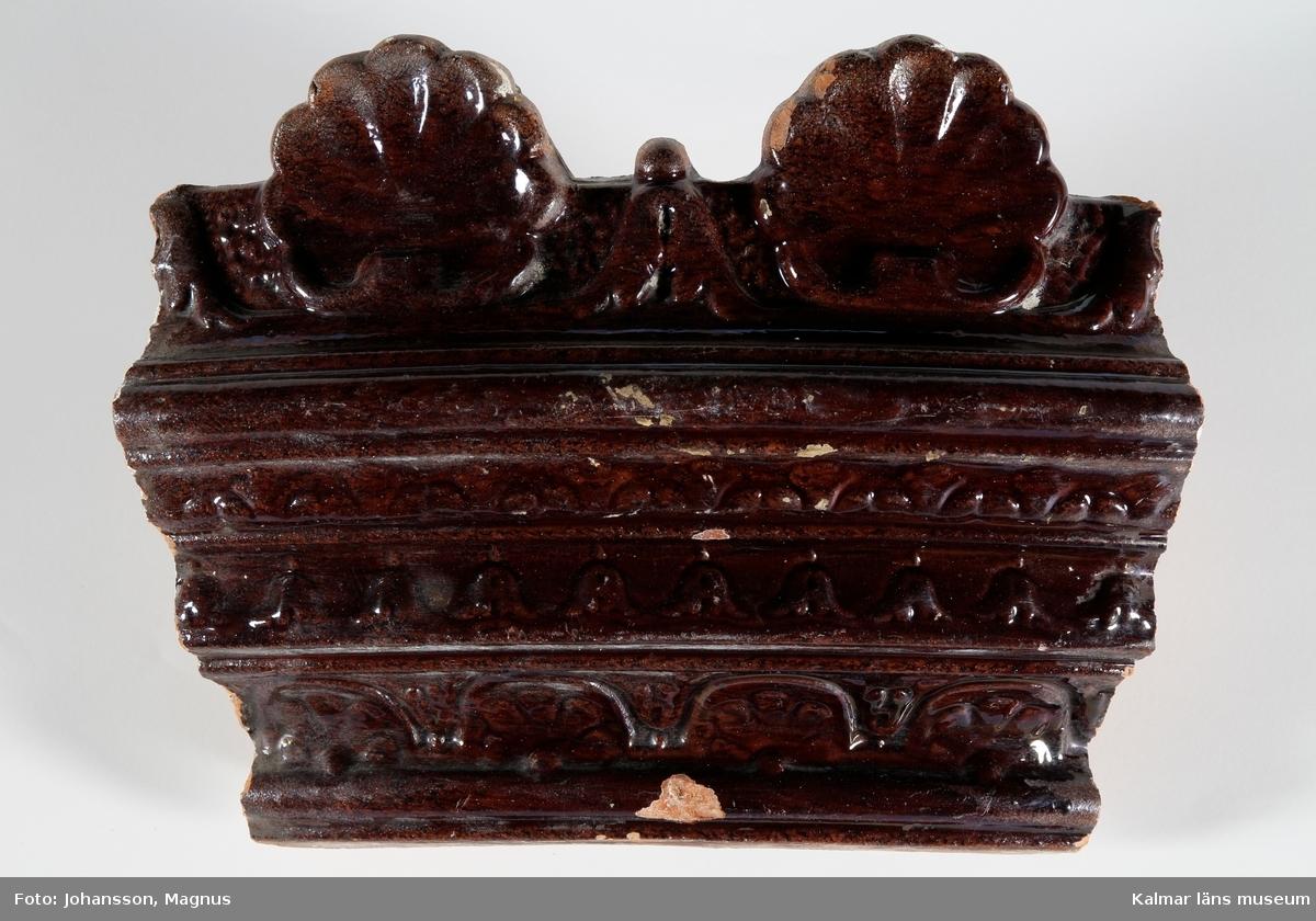 """KLM 28165:1:1-8. Kakelugn. Rund ugn med rödbrun glasyr, heltäckande reliefdekor med geometriska mönster och bladmotiv. Tillverkad av gulröd lergodslera. Drejad rump. Datering, 1870-tal. Förteckning över ugnens samtliga delar, med mått inom parentes, gjord i samband med inventering 1964: :1. 17 st fasadkakel (29,5x23,5 cm)        1            -""""-     (30x23,5 cm)        1            -""""-     (27,5x23,5 cm)        2            -""""-     (24,5x23 cm)        4            -""""-     (24x23 cm)        1            -""""-     (29x11 cm)        1            -""""-     (31,5x23,5 cm)        2            -""""-     (32x23,5 cm)        1            -""""-     (32x25 cm)        1            -""""-     (31x24 cm)        1            -""""-     (31,5x12 cm) :2.   6 st livkakel (23,5x25 cm) :3.   3 st listkakel (6,5x28 cm)        1       -""""-      (6,5x26 cm)        4       -""""-      (12x28 cm) :4.   1 st krönkakel (23x25 cm)        3        -""""-        (23x28 cm)        1        -""""-        (20x26 cm)     :5. 11 st kakelfragment :6.   2 luckor av järn samt ram, 30,5x27 cm. :7.   3 sotluckor av mässing och järn, dia: 10,5 cm. :8.   1 spjäll av järn, 53,5x15 cm."""