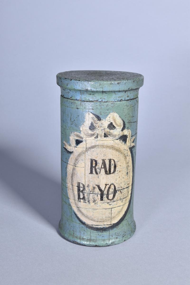 Ståndkärl av grönmålat trä, cylindriskt med plant lock. Svart text inom oval med bandrosett.