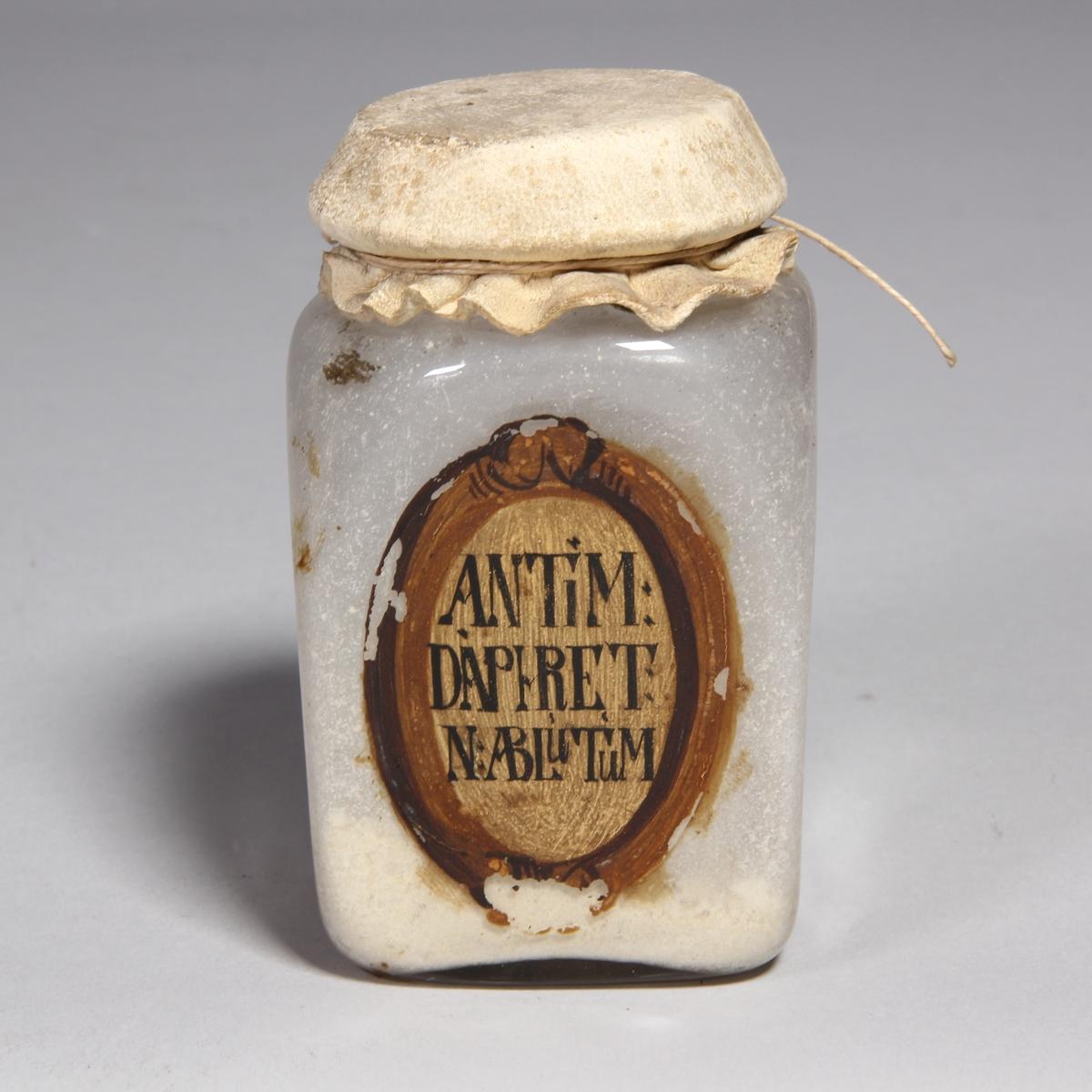 Burk av klart glas, kvadratisk med runt överbundet lock av skinn fäst med snöre. Innehåller vitt puver.