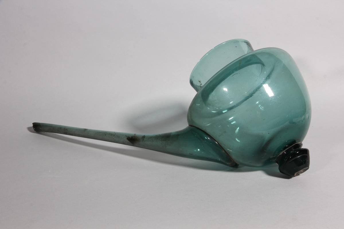 Hjälm, retortliknande, av gröntonat glas. Urnformad med lång pip samt knopp.