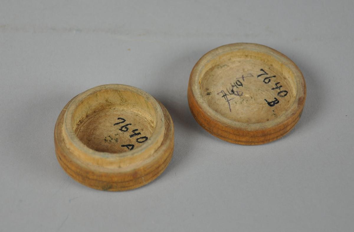 Liten rund eske av tre, med avtagbart lokk. Det er innrisset konsentriske sirkler på over- og undersiden av esken.   Enkelte flekker på bunn og sidene