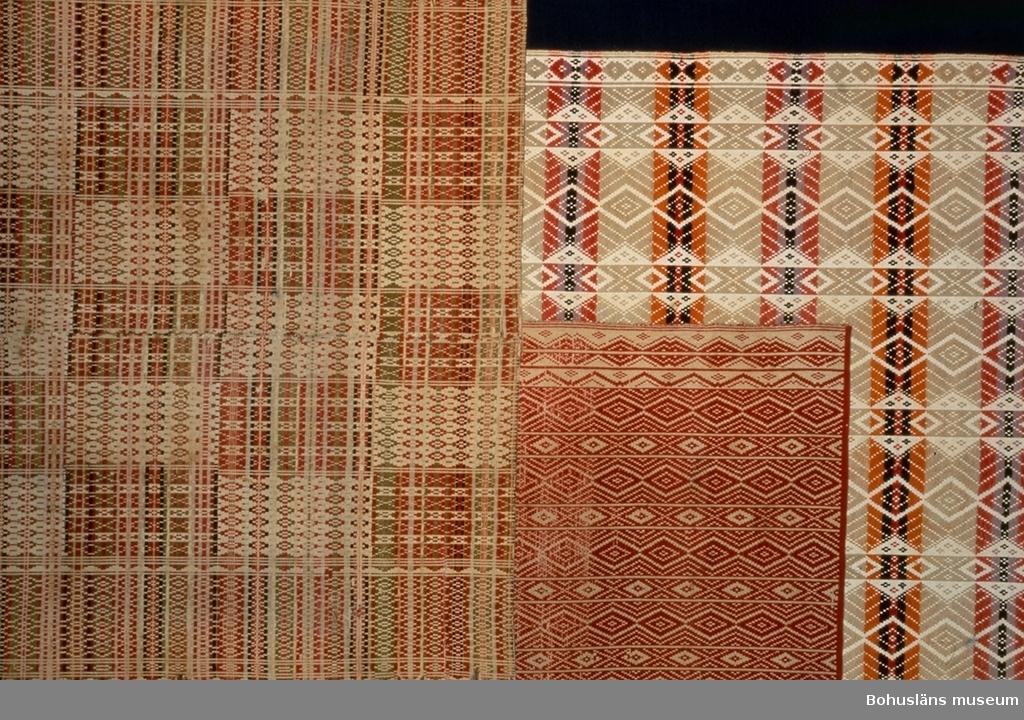 Täcket är avbildat till höger på föremålsfoto 2. Täcket till vänster är UM016022, täcket i mitten är UM016034.   Täcke vävt i ett stycke utan mittsöm. Varp och botteninslag av oblekt bomullsgarn. Mönsterinslag av tvåtrådigt ullgarn. Mönstret består av smala rombmönstrade bårder längs kanterna och innanför dem omväxlande smala och breda längsgående ränder mönstrade med romber. Inslagets färger bildar däremot ränder på tvären; breda ljust blåtonat gröna ränder omväxlande med lika breda ränder uppbyggda av smalare ränder i gulrött (orange)/svart/rött eller ljusrött/svart ljust rödblått (violett). Enligt litteraturen förekommer denna rombmönstrade typ av upphämta bara i Bohuslän. Garnet färgat med syntetiska färgämnen. Väverskan Matilda Nilsdotter var född 1860 på Stripplekärr (Sandvadet) Ödsmål?. Hon hade lärt vävkonsten av sin mor Johanna-Maria född i Ödsmål. Matilda var professionell väverska på Hisingen från slutet av 1870-talet till 1900. Hon vävde dukar, sängtäcken (överkast), lakan, tyger till kjolar och kostymer mm. Hon var 2-3 månader i sänder på olika gårdar, huvudsakligen i Tuve men även i Backa församling.  (Namn på ställen där hon vävt: Tången, Tuve, Skändla, Skogome, Kärralund.) 1900 återvände hon till Ödsmål och gifte sig med Alfred Andreasson. Matilda och Alfred var föräldrar till givaren Birger Andreas- son född 1902 i Bräcke i Ödsmål. (Jfr Samuel Lydéns skrift om Ödsmål där han bl.a skriver om vävning på 1700-talet.) Upptill på baksidan finns påbörjad montering för upphängning, tänkt att ha vid demonstration av montering. Litet hål vid ena kortsidan. Gulnat. Blekt, bitvs färgförändrat. Utstickande trådar här och var.  Litt; Berg, Kerstin, Selma Johansson - väverska och hembygdsforskare i Södra Bohuslän, Skrifter utgivna av Bohusläns museum och Bohusläns hembygdsförbund Nr 41, Uddevalla 1991, sid 178-186.  Lychou, Kerstin, Hemslöjd och folkkonst i Bohuslän, Warne förlag AB, Partille 1996, sid. 156-160.  Sekora, Ann-Britt, Upphämta i Bohuslän (uppsats vi