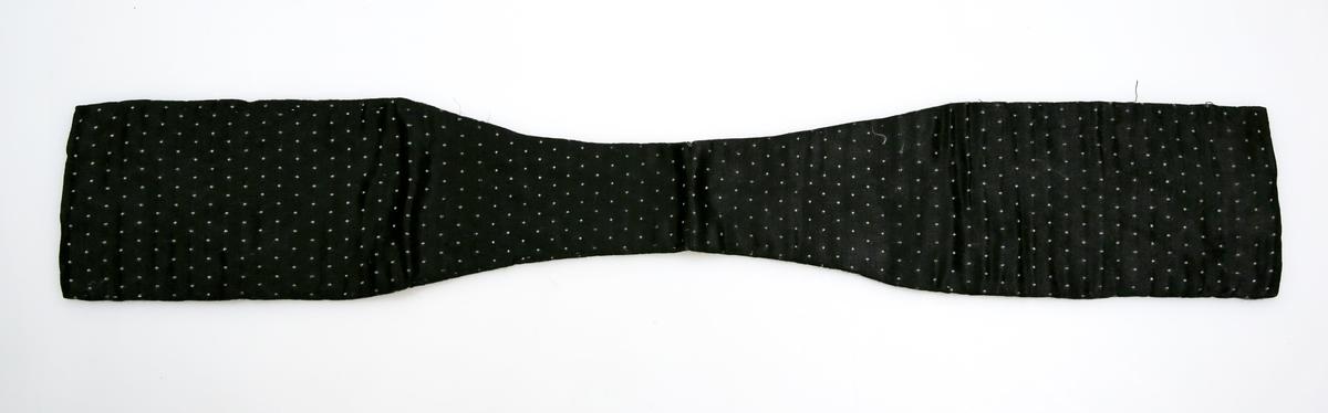 Innvevd små hvite prikker. Søm på midten bak. To symmetriske biter. Hvitt silkefor uten midtsøm sydd på for hånd med faldesting
