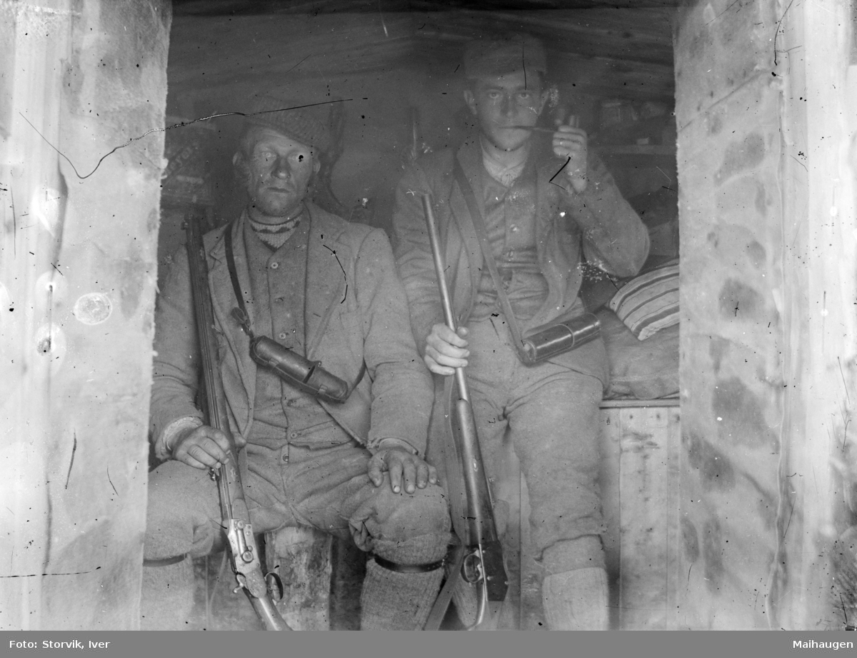 To jegere sitter med børser inne i ei bu