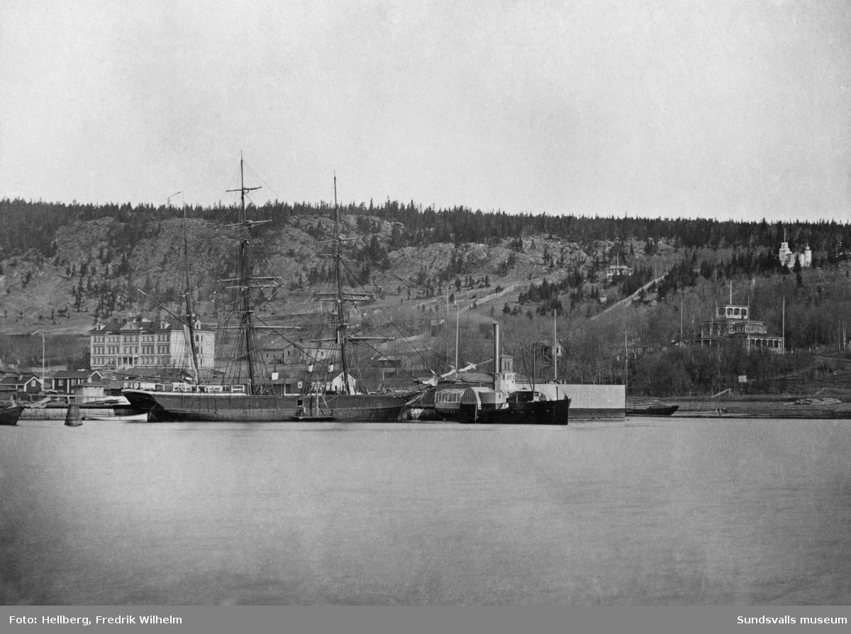 """Hamnen med ett segelfartyg och hjulångaren """"Swartvik"""". På bilden till vänster Sundsvalls lasarett, i mitten på bilden bakom hjulångaren syns ett torn vilket hör till kallbadhuset och till höger på bild syns Tivoli. Bildtext i allbum """"Hamnen, Lasarettet, badhuset och Tivoli i bakgrunden."""""""