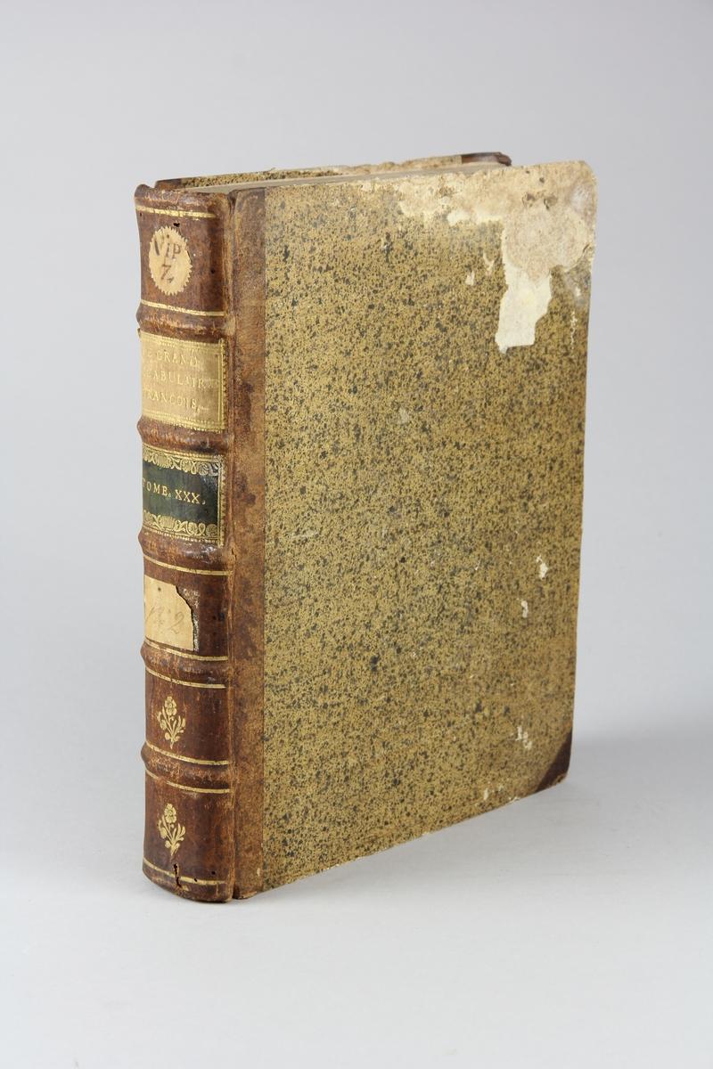"""Bok, halvfranskt band """"Le grand vocabulaire francois"""", del 30, utgiven i Paris 1774. Band med pärmar av papp med påklistrat stänkt papper, hörn och rygg av skinn med fem upphöjda bind med guldpräglad dekor, titelfält med blindpressad titel och ett mörkare fält med volymens nummer. Med stänkt snitt. Påklistrade etiketter märkta  med bläck."""