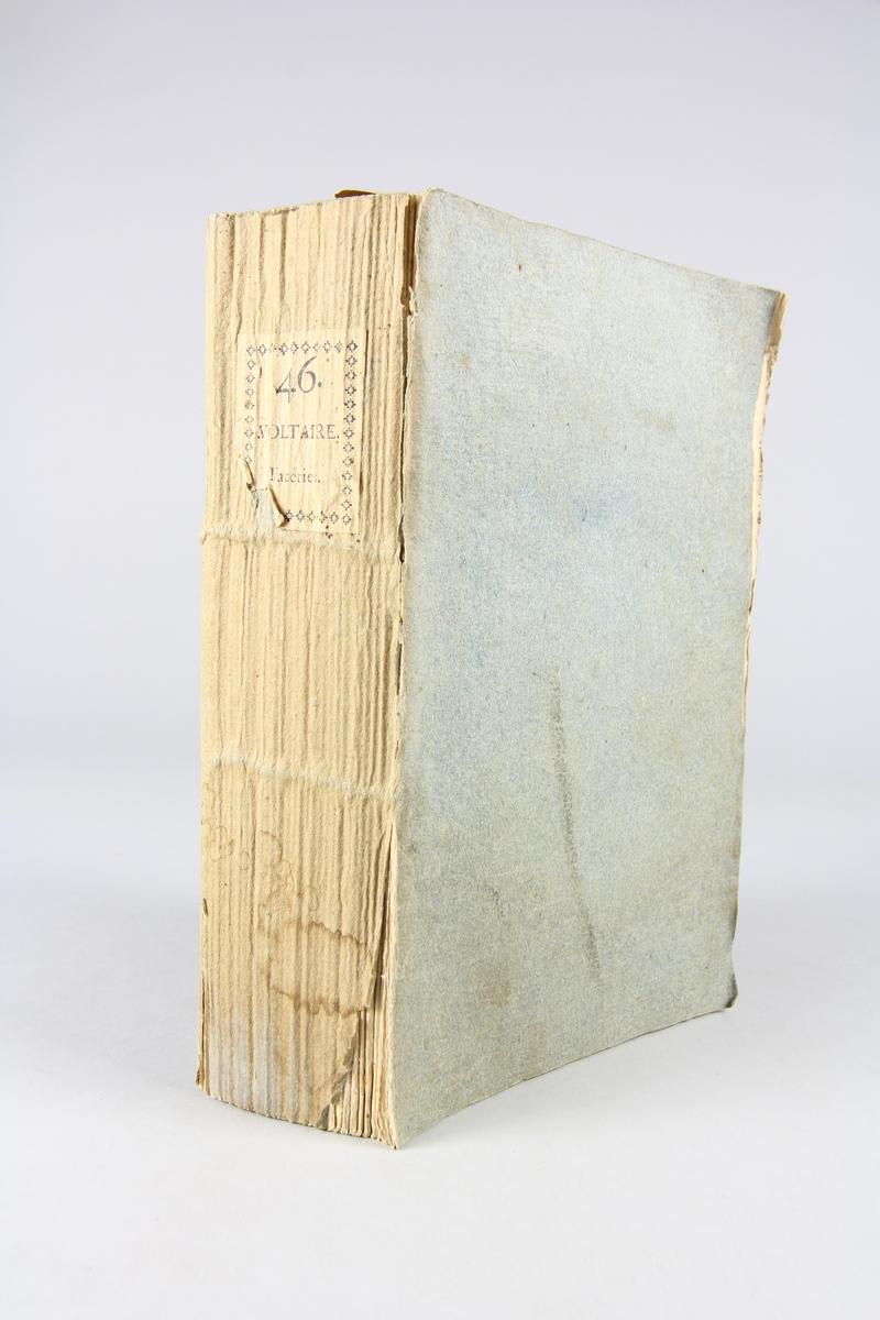 """Bok, pappband,""""Oeuvres complètes de Voltaire."""" del 46, tryckt 1785. Pärm av gråblått papper, på pärmens insidor klistrade sidor ur annan bok. skurna snitt. På ryggen pappersetikett med tryckt text med volymens namn och nummer. Ryggen blekt."""