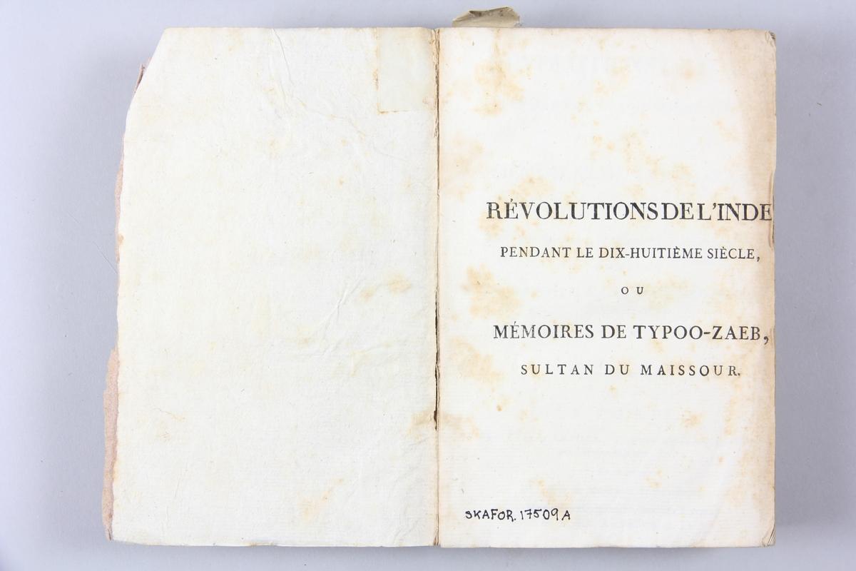 """Bok, pappband, """"Révolutions de l´Inde"""", del 1, tryckt 1796 i Paris. Pärmar av ljusbrunt papper, blekt rygg med tryckta etiketter med bokens titel och nummer, otydlig text. Skuret snitt."""