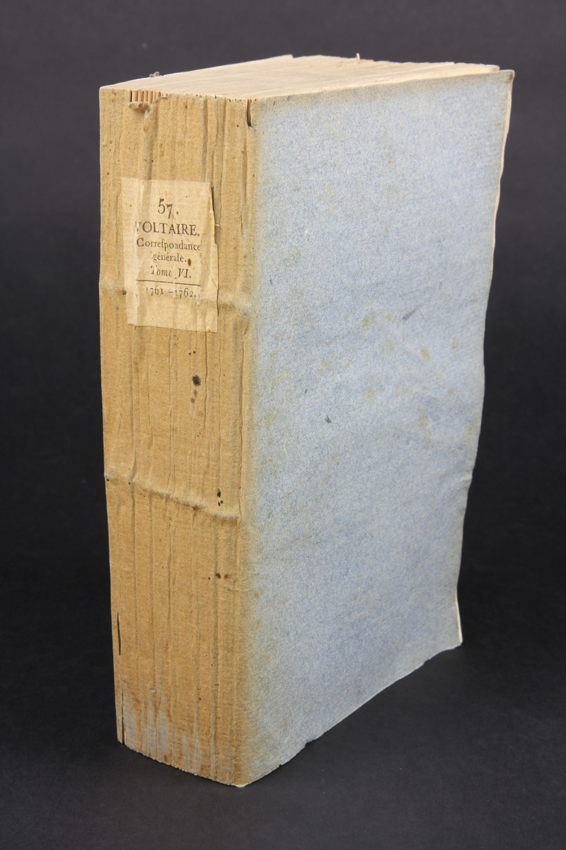 """Bok, häftad, """"Oeuvres complètes de Voltaire, Receuil de lettres 1761-1762"""", del 57, tryckt 1785. Pärm av gråblått papper, insidorna med inklistrade sidor ur annan bok, skurna snitt. På ryggen pappersetikett med tryckt text samt volymens namn och nummer. Ryggen blekt."""