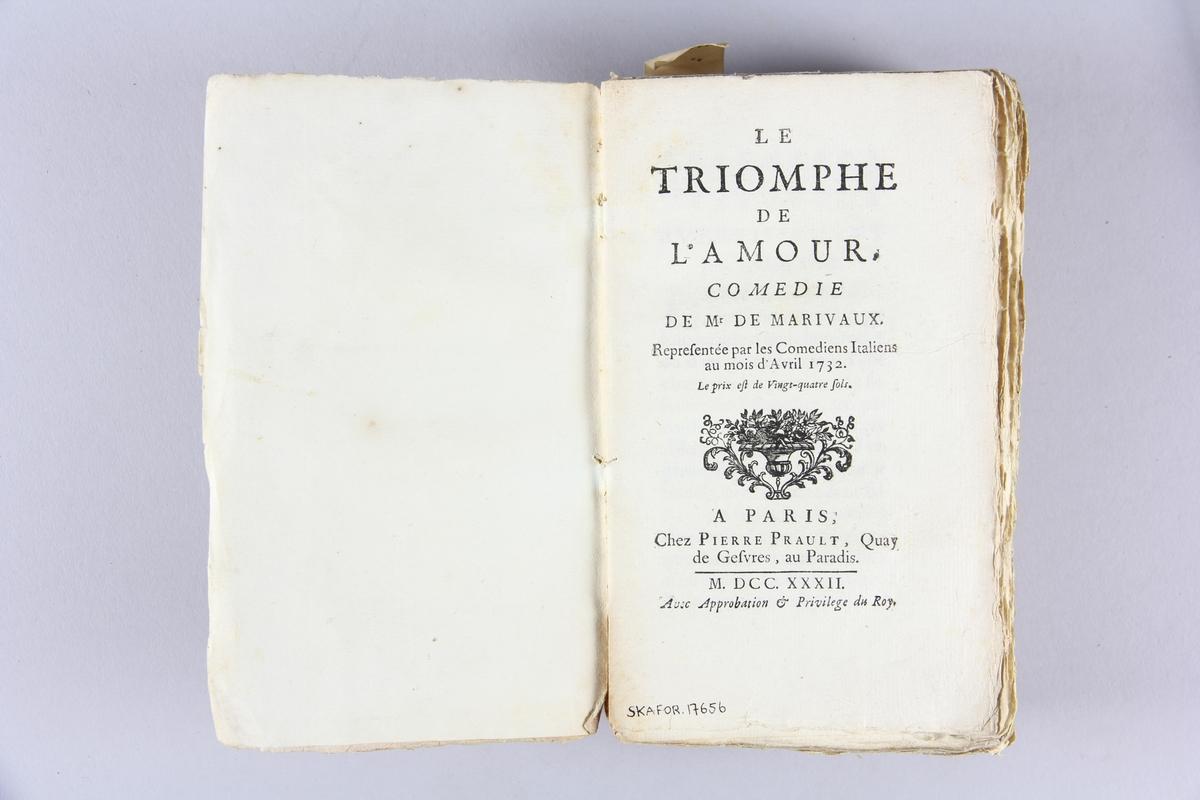 """Bok, häftad, """"Le Triomphe de l'amour"""". Pärmar av marmorerat papper, oskuret snitt. Blekt rygg med etikett med titel och samlingsnummer."""