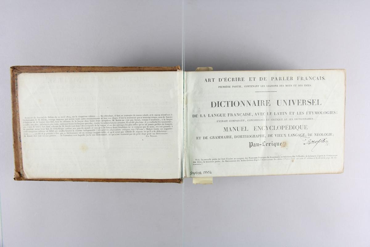 """Bok, skinnband """"Dictionnaire universel"""". Guldpräglad rygg med röd präglad etikett. Marmorerat papper på pärmarnas insidor. Blåmarmorerat snitt. Namnteckning på försättsbladet."""