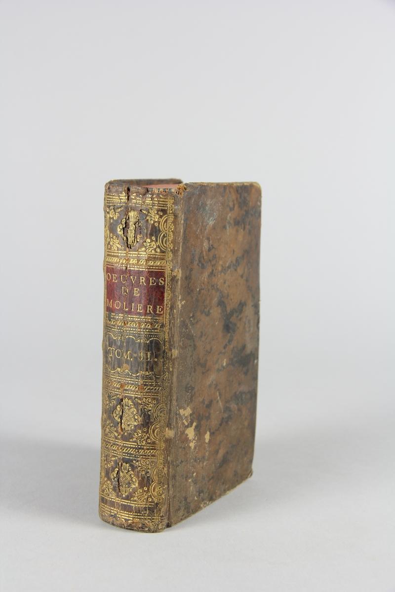 """Bok, """"Oeuvres de Molière"""", del 2. Skinnband med guldpräglad rygg, fält med titel och volymnummer. Marmorerat papper på pärmarnas insidor. Rött snitt. Illustrerad med kopparstick."""