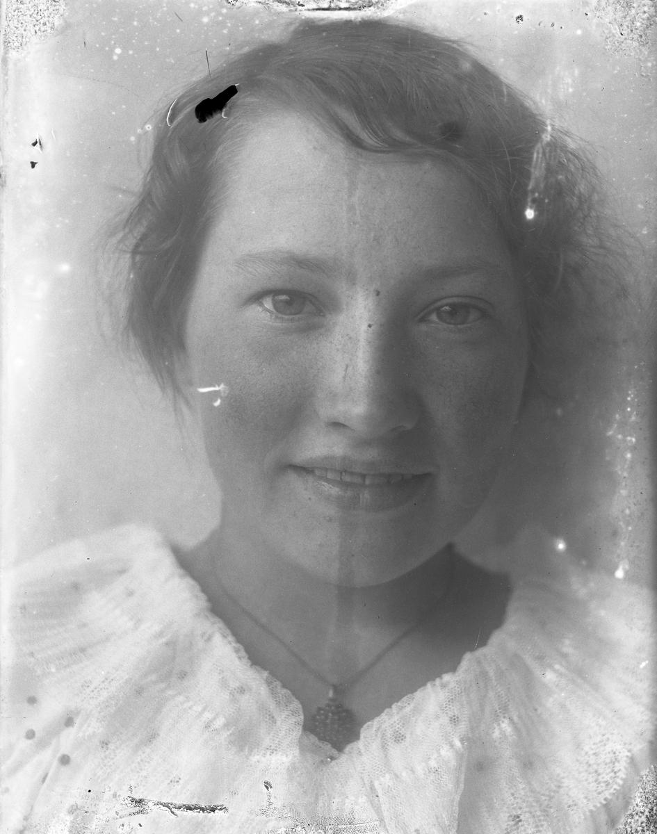 Porträtt av Annie Hultén i vitt med ett halsband, troligen med granater, om halsen.