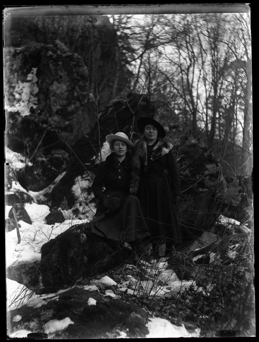 Signe och Eva fotograferade i skogen. Lite snö ligger på marken.