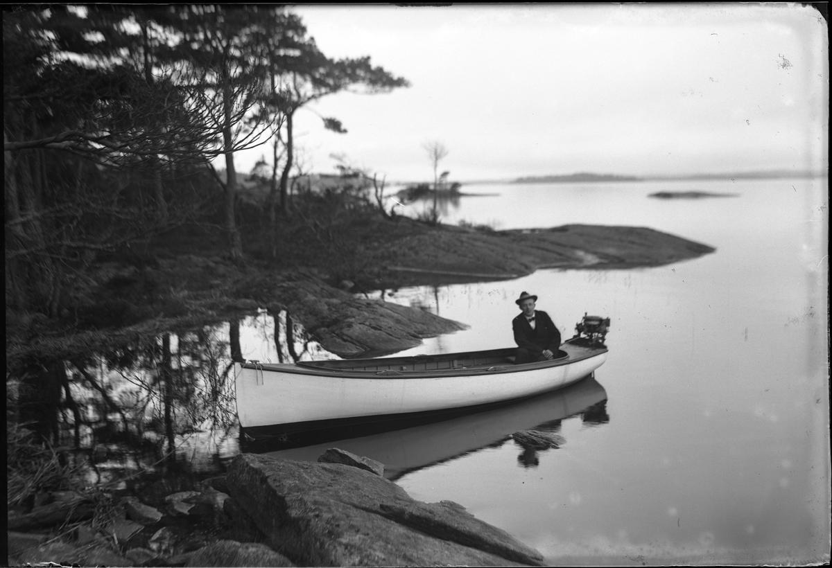 John Hjelm sitter i en vitmålad motorbåt i Norsekären. Han har mörk kostym, fluga och hatt.