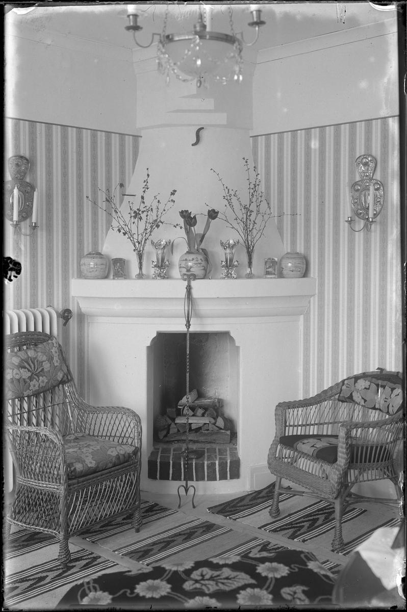 """Två korgstolar med stoppade dynor står framför en vitkalkad eldstad. På spiselkransen står vaser av porslin, keramik och glas och på golven ligger vävda mattor. Hemmet är nybyggt vid tiden för fotograferingen. I fotografens egna katalog står: """"Interiör för Fröken Bruzewitz""""."""