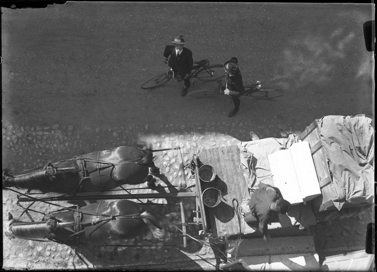 """Foto på två män på varsin cykel samt en man på en kärra dragen av två hästar. Bilden är tagen från fabrikstaket till Alingsås Väveri och i fotografens anteckningar står det """"Victor, Frodelius & Gustafsson""""."""