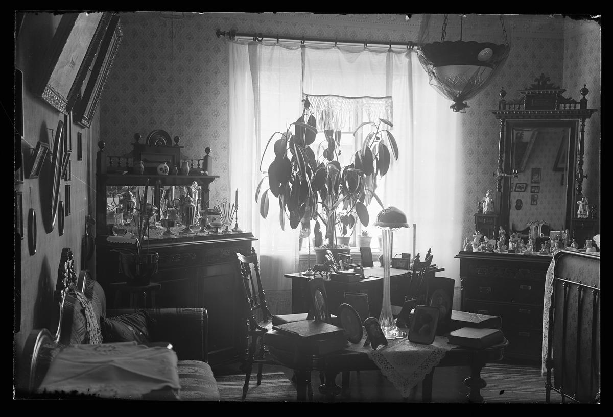 Interiörbild från Tekla Svenssons rum. Längs ena väggen står en soffa och framför den ett bord med fotoramar och album. I rummets bortre två hörn står en spegelskänk respektive en spegelbyrå, båda med vaser och prydnader. Emellan dessa, framför ett fönster, finns ett skrivbord och i bildens ena hörn, mittemot soffan står en järnsäng. På väggarna hänger tavlor och i taket en lampa täckt av svart tyll.