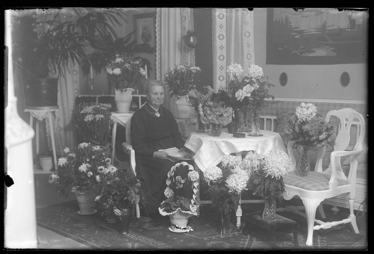 Fru Axelsson fotograferad med gratulationstelegram i handen och omgiven av blommor i samband med sin 50årsdag.