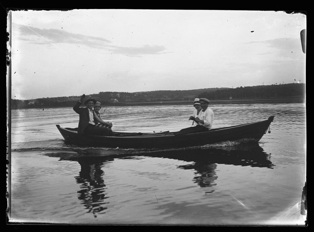 """Två män och två kvinnor sitter i en bår ute på vattnet. Båda männen röker och den ena vinkar mot kameran. I fotografens egna anteckningar står det """"Thorsells båt (Hippa på Norseskären)"""""""