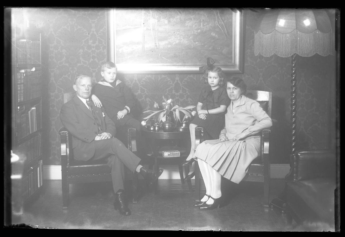 Familjen Nilsson porträtterade i ett bibliotek eller finrum. Pappa Hjalmar Nilsson sitter i en fåtölj med Bengt Fredrik Nilsson sittande på armstödet. På andra sidan ett litet bord sitter mamma Gerda Teresia Amalia Nilsson med dottern Gerd Anna-Lisa på armstödet.