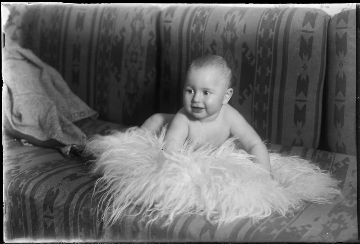 """En bäbis ligger på en fäll i en soffa. I fotografens egna anteckningar står det """"Fredrikssons pojke""""."""