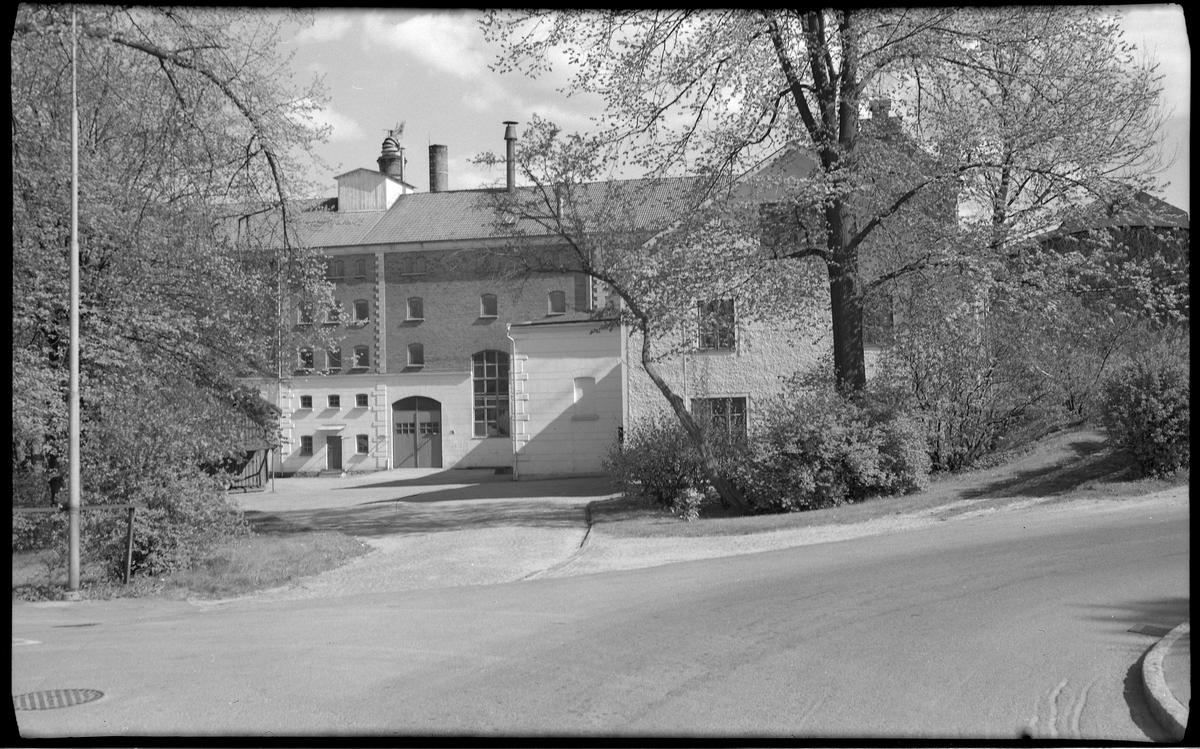 En stor stenbyggnad, rött tegel och ljus putsad stenfot, med en tillbyggnad i vinkel.  Alingsås Bryggeri AB, Bryggaregatan 2 i kv Bryggaren.   Bryggeri-verksamheten lades ned 1972 och under 1996 och 1997 revs fastigheten.