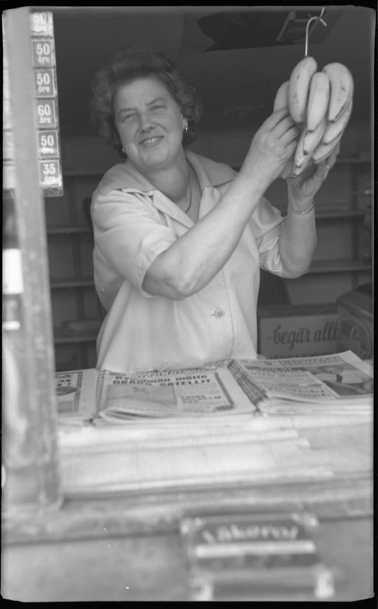 Centralkiosken på Boråsvägen 25.  Fru Risberg står bakom luckan, disken, in till kiosken. Lite arrangerat håller hon en bananklase i handen, klasen hänger på en krok. Framför kvinnan ligger olika dagstidningar i högar, bredvid varandra.  Kvinnan har en ljus klänning med stor krage och knappar fram.  Innehavare Gunnar Risberg.   Kiosken flyttades 28.6.1965 till Saxebäcken, för att användas som sommarstuga.