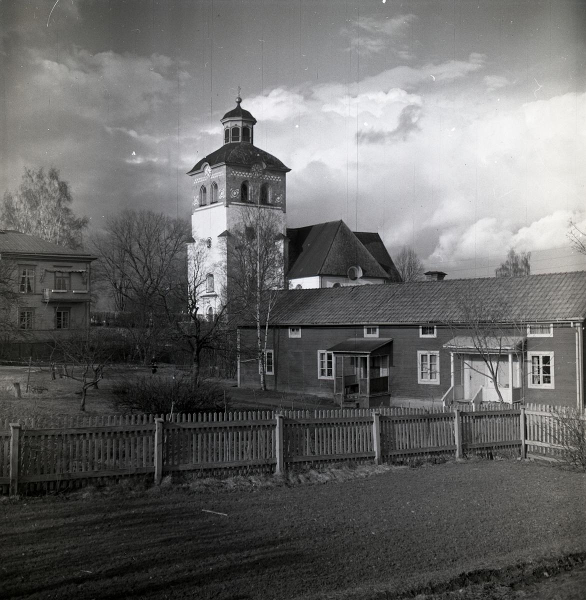 Bollnäs kyrka bakom kringliggande byggnader.