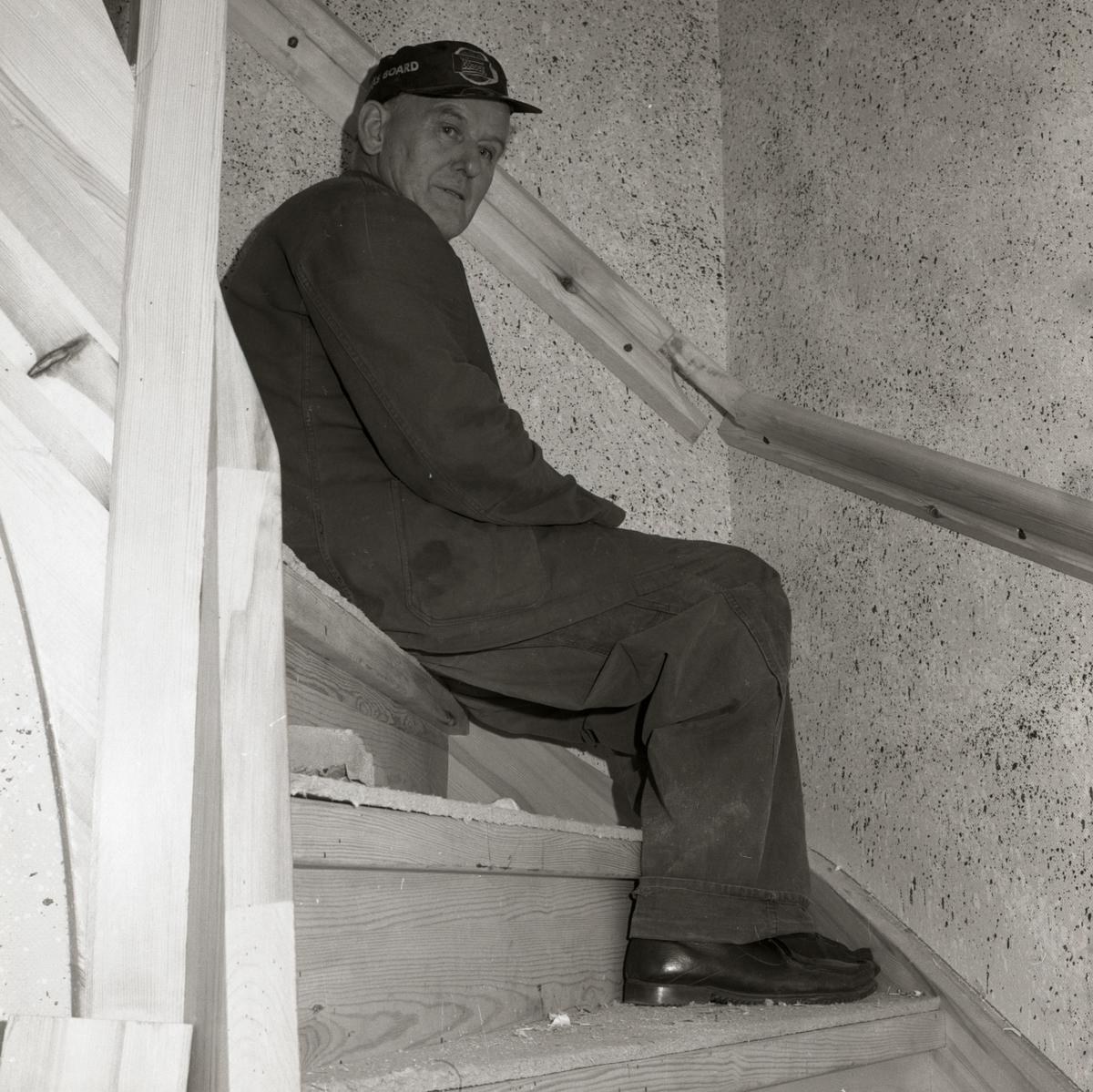 En man sitter i en trappa där väggarna är stänkmålade, 1967-68 vid gården Sunnanåker.