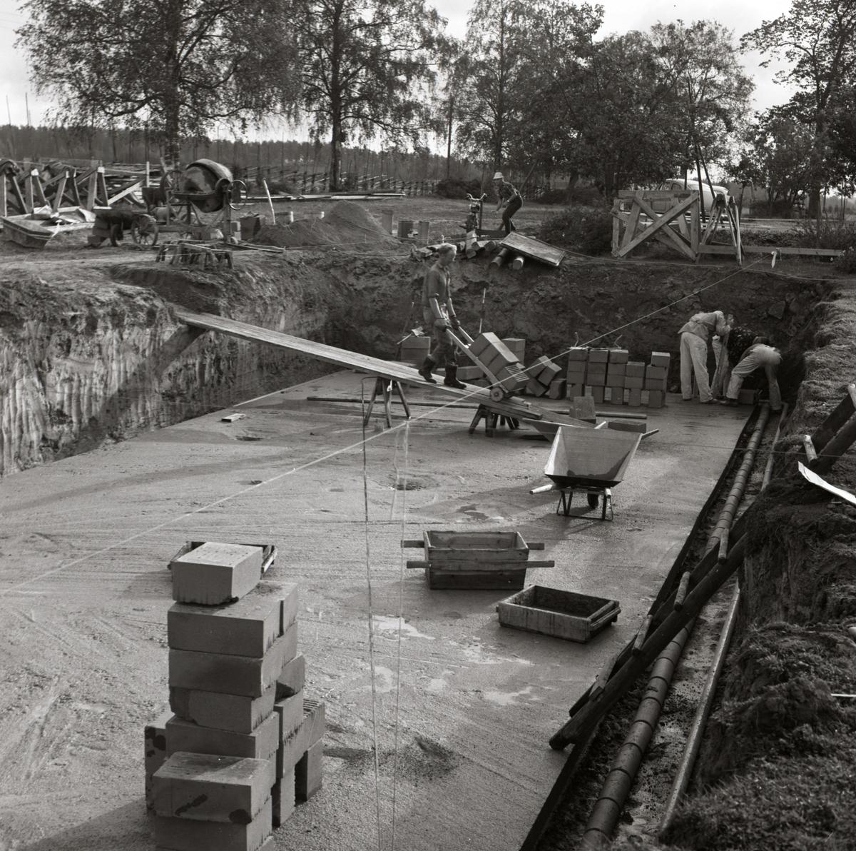 En man kör en skottkärra med tegel till husgrunden vid byggnation av hus vid gården Sunnanåker. Två andra män arbetar med att mura tegel, 1967.