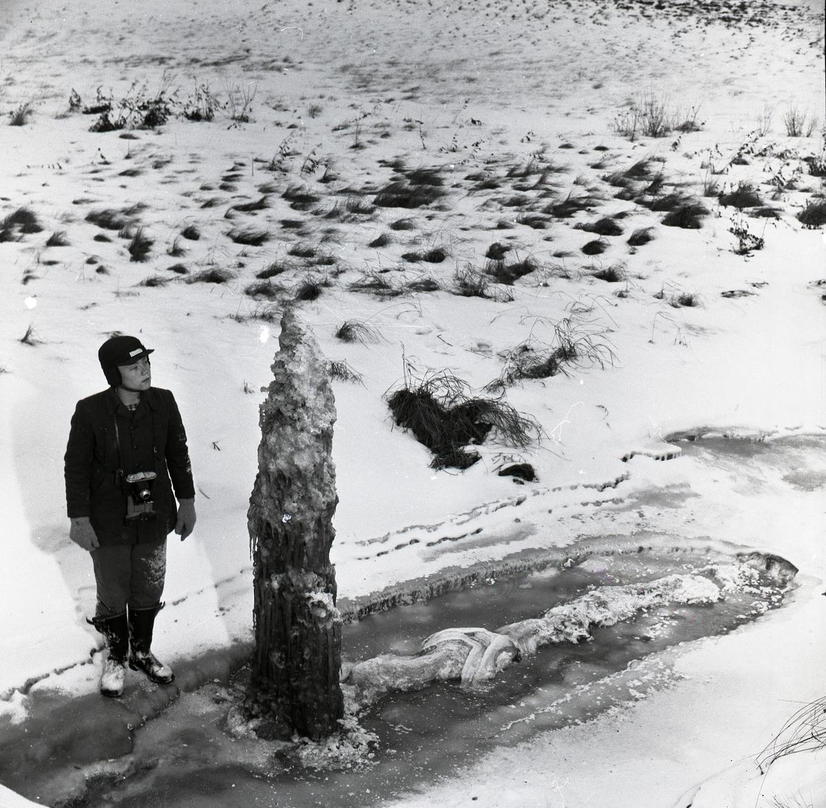 En pojke står intill en ispelare vid Peranders bron den 19 december 1957.