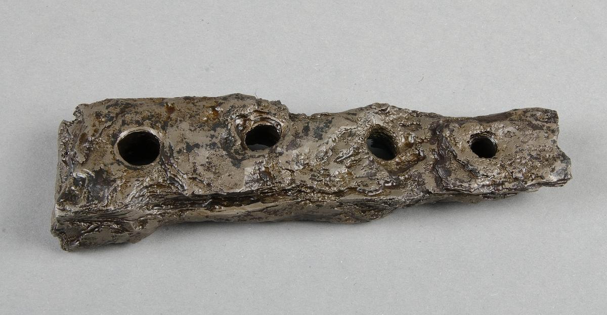 Föremål i järn, kraftigt korroderad järnklump. I brottytan synligt taperande rygg av kraftigt järn.