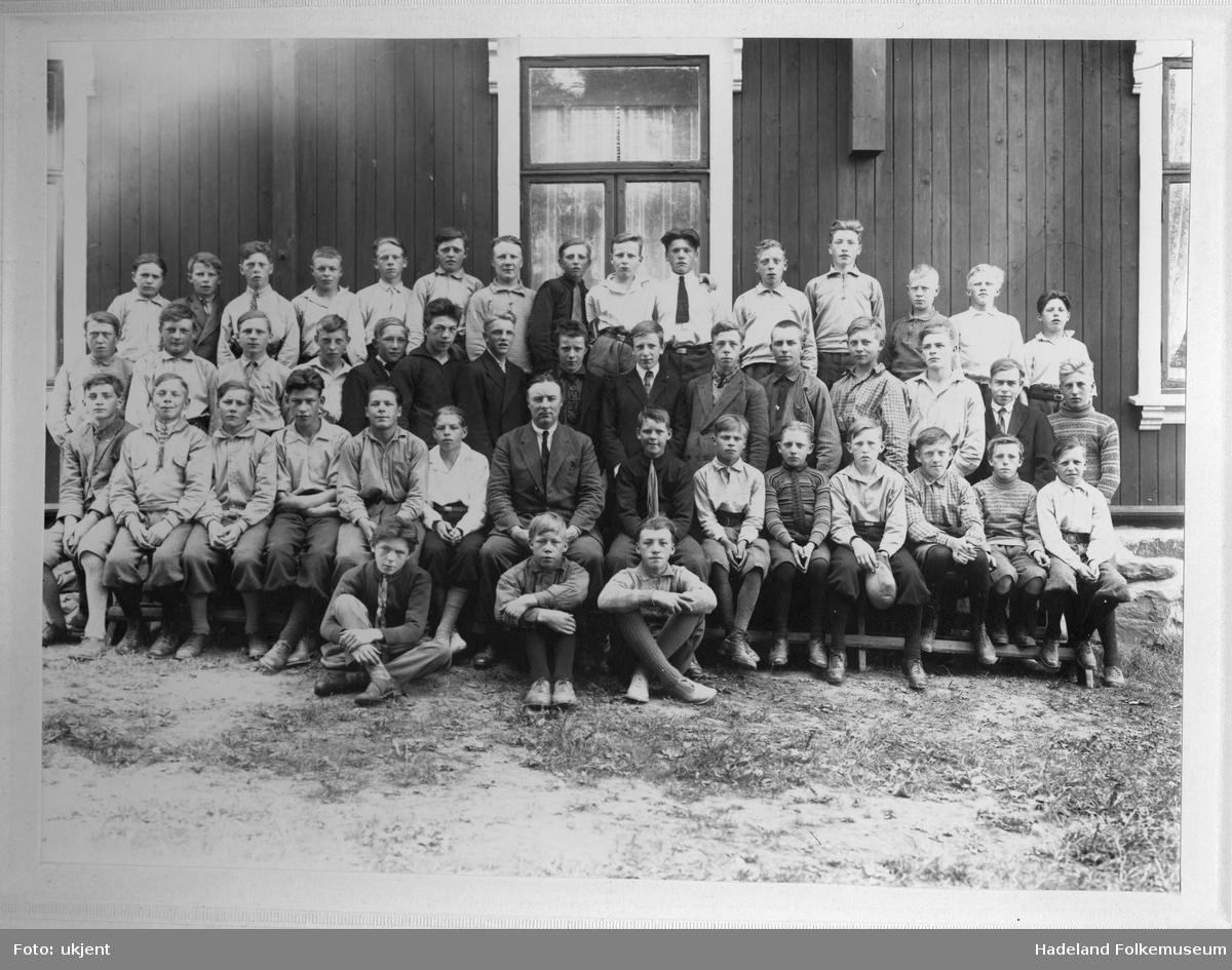 Konfirmanter, kun gutter, med sogneprest Kinge samlet utenfor ungdomslokalet Solvang.