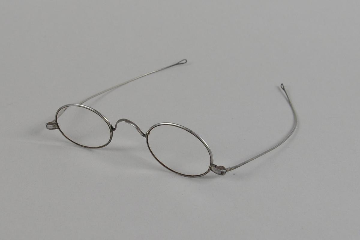 Ovale briller med metallinnfatning. Brillestengene har en liten oval ring ytterst.