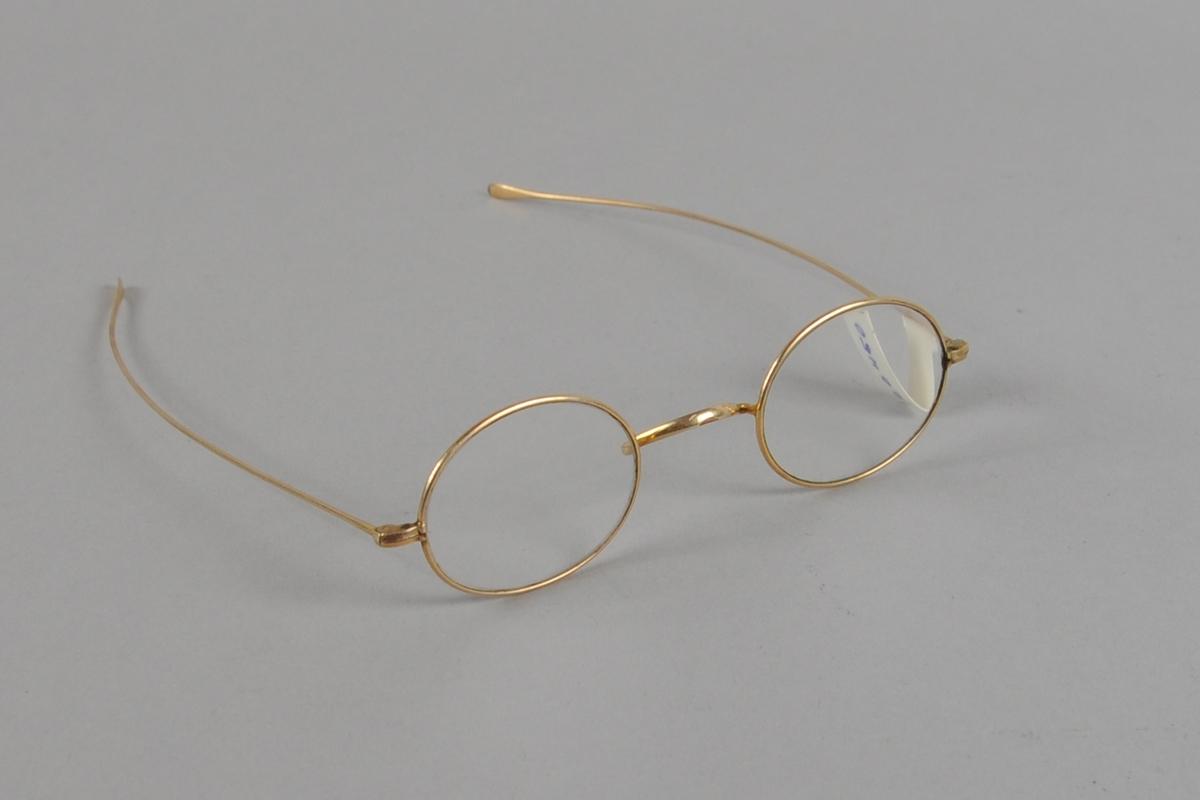 Ovale briller med gullfarget metallinnfatning. Lange brillestenger.