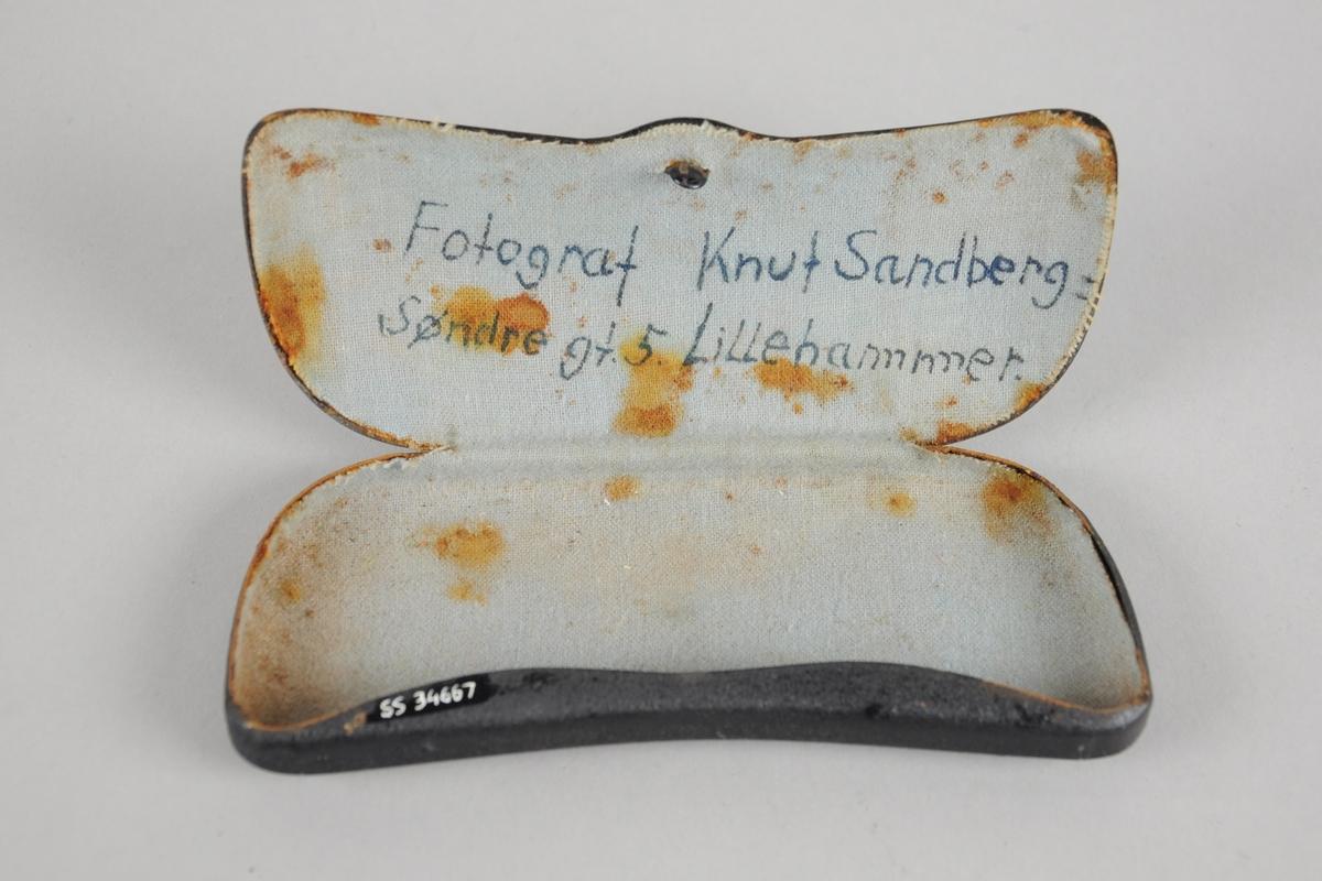 Brilleetui av metall foret med lyseblått bomullsstoff. Eierens navn er skrevet med håndskrift på innsiden av lokket.