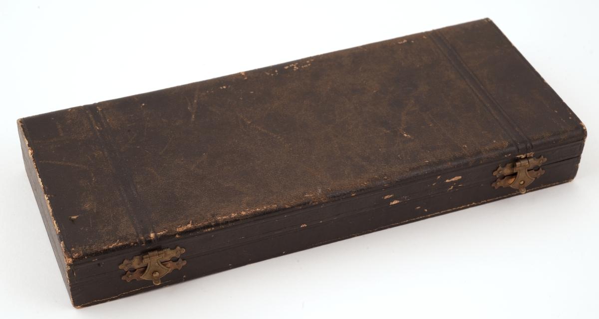 Forgylt sølvskje i original skinntrukket eske med fôr av gulbrun fløyel. Stemplet «830S M. Hammer Bergen» på baksiden av bladet. Rennessanseform med langt, tynt, rundt skaft og rundt blad. Skaftet inndelt i vulster, hulkiler og profilerte, kuleformede ledd avsluttet med fire kjerubhoder øverst. Bladet har gravert, barokkpreget akantusdekor på innsiden. Form og gravering henger altså ikke helt sammen.