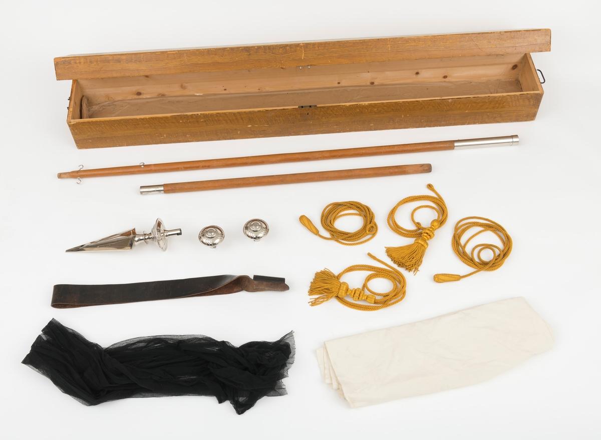 """Fane, fagforeningsfane, med tilhørende utstyr: todelt stang med metallholker, 1 fanespyd i metall, halvkuleformet pynt 2 stk,   4 snorer (2 med dusker, 2 med """"kongler""""), sørgeflor, bæresele  (bandolær) og varetrekk (beskyttelestrekk under opbevaring). Faneduken og tilhørende utstyr ble oppbevart i ei trekasse.     Faneduken:  Den rektangulære faneduken er utført i grønn silke med frynser i gyllen tråd (silkeaktig tråd), kantet med gullsnorer (forgylte snorer).  Fana har kappe av rød fløyel i overkant. Kappa omslutter fanedukes tverrstang, rundstav av tre. Midt på denne rundstaven er det en øyekrok til å henge faneduken til fanastanga når den bæres. Kappas nedre del er skåret i en bøyd form som flukter med fagforeningsnavnet rett under. I nedre kant har kappa påsydde frynser i gyllen tråd.  Fanedukens nedre kant har fliker, splitter, tunger, med påsydde frynser i gylden tråd.  På fanedukes framside er fagforeningens navn: Klevfoss avd. 60 av NPF påsydd med """"gullbokstaver"""". Fana er bemalt både på forsiden og baksiden. På framsiden ses  en oppadstigende sol mot en blå himmel omsluttet av to eikegreiner. På den blå himmelen er bokstavene NPF påført i """"gullskrift"""" , en papirrull er stukket gjennom åpningen i P-en.  De to eikegreinene er forbundet av to hender som møtes i et håndslag. (Kan se ut som om det er et håndslag mellom arbeider og funksjonær, arbeidsbluse og dress.) Håndslaget ses mot en rød bakgrunn utformet som et skjold.  På fanedukens bakside er ses teksten SAMHOLD ER MAKT og et påmalt håndtrykk.  Håndtrykket omsluttes av to eikegreiner bundet sammen av et rosafarget bånd.  Oppbevraingskassa (etuiet):  Alt utstyret til fana ble oppbeavart i ei trekasse med lokk som utvendig målt er 185 cm lang , 25 cm bred og 25 cm høy. I hver kortende på kassa er det påmontert bevevgelige metallhåndtak, som letter forflytningen av den.  Håndtakene er festet til ei metallpalte som er skrudd fast med 5 skruer i kassa. Kassa (etuiet) er utvendig malt med lysebrun farge, trolig """