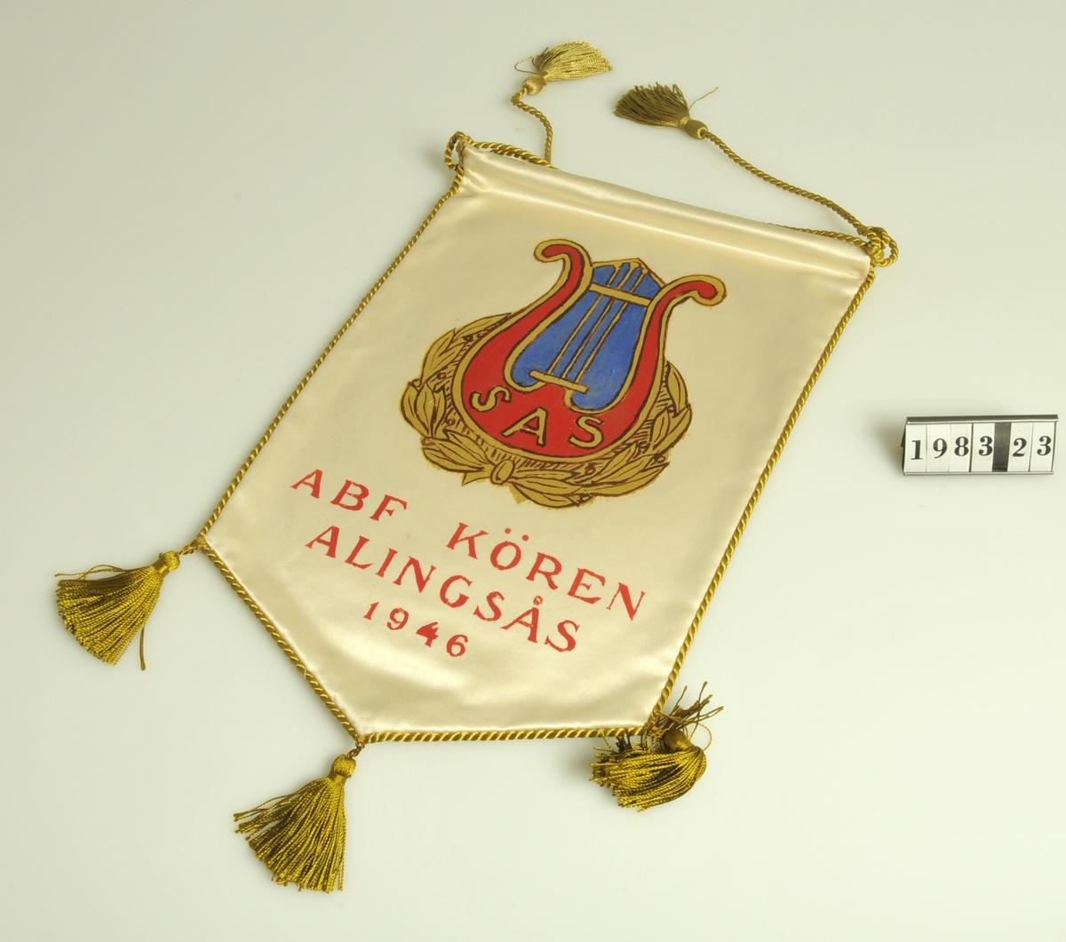 Tyg av vitt siden bemålat med emblem i form av lyra i rött, blått och guldfärg.  Inom lyran bokstäverna: S A S = Svenska Arbetarsångarförbundet.  På standarets nedre del texten: ABF-KÖREN ALINGSÅS 1946 målat i rött.  Silkestofsar och -snoddar inramar standaret.  Storlek: 18 x 28,5 cm.  Föremålet tillvarataget i källaren på Rådhuset vid inventering i mars 1983.  Överlämnat i mars 1983 av kommunsekreterare Tord Jansson, Alingsås.