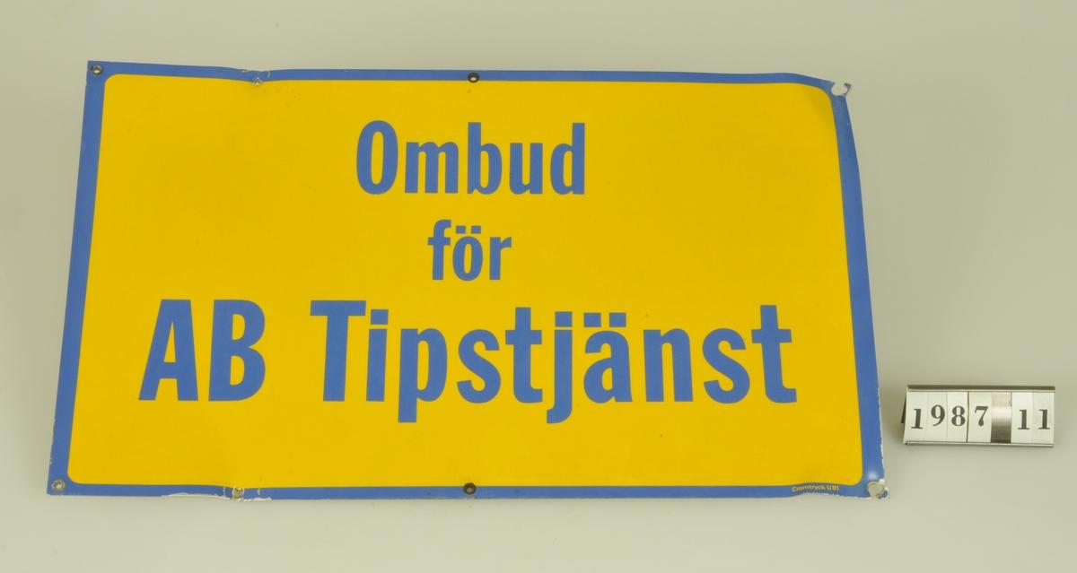 """Text: """"OMBUD  FÖR AB TIPSTJÄNST"""". Blå text och kant mot gul botten.  Kommer från livsmedelsaffären Oskar Nilssons Eftr. Lärkvägen 15, Alingsås. Affären etablerades 1906 och lades ned i juni 1986."""