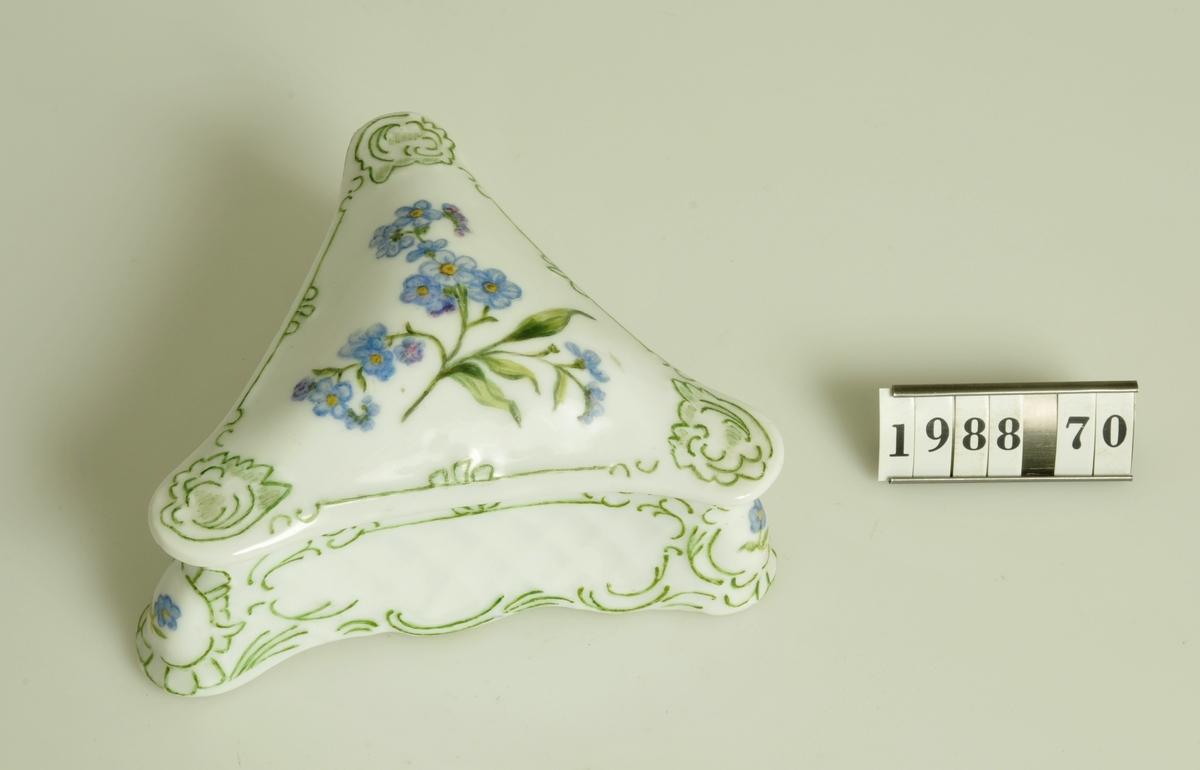 "Trekantig form. Handmålad enkel blomdekor. Kolorerad. Askens botten: ""Nina L-n 23.12. 1902 af H.H""."