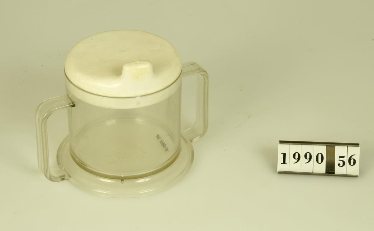 Mugg med piplock, tillverkad av genomskinlig resp vit hårdplast. Använd av givarens son vid all form av drickande eftersom han vägrade använda nappflaska.