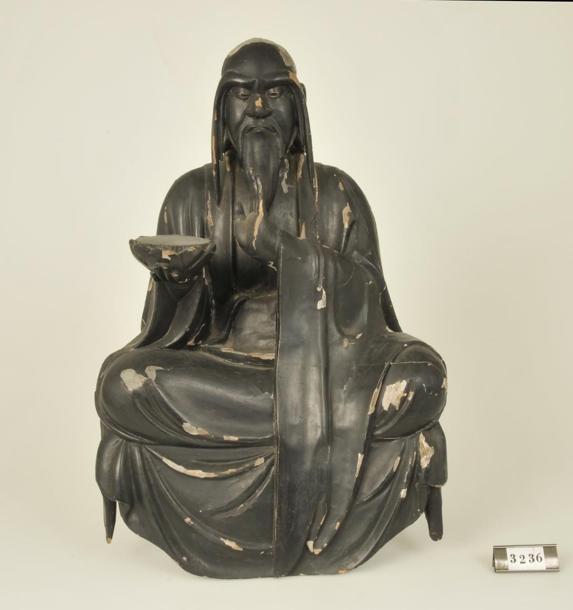 Träskulptur föreställande en man i sittande ställning. Håller i höger hand en tom bricka. Målad i svart.  Har tillhört de Adelsköldska samlingarna.