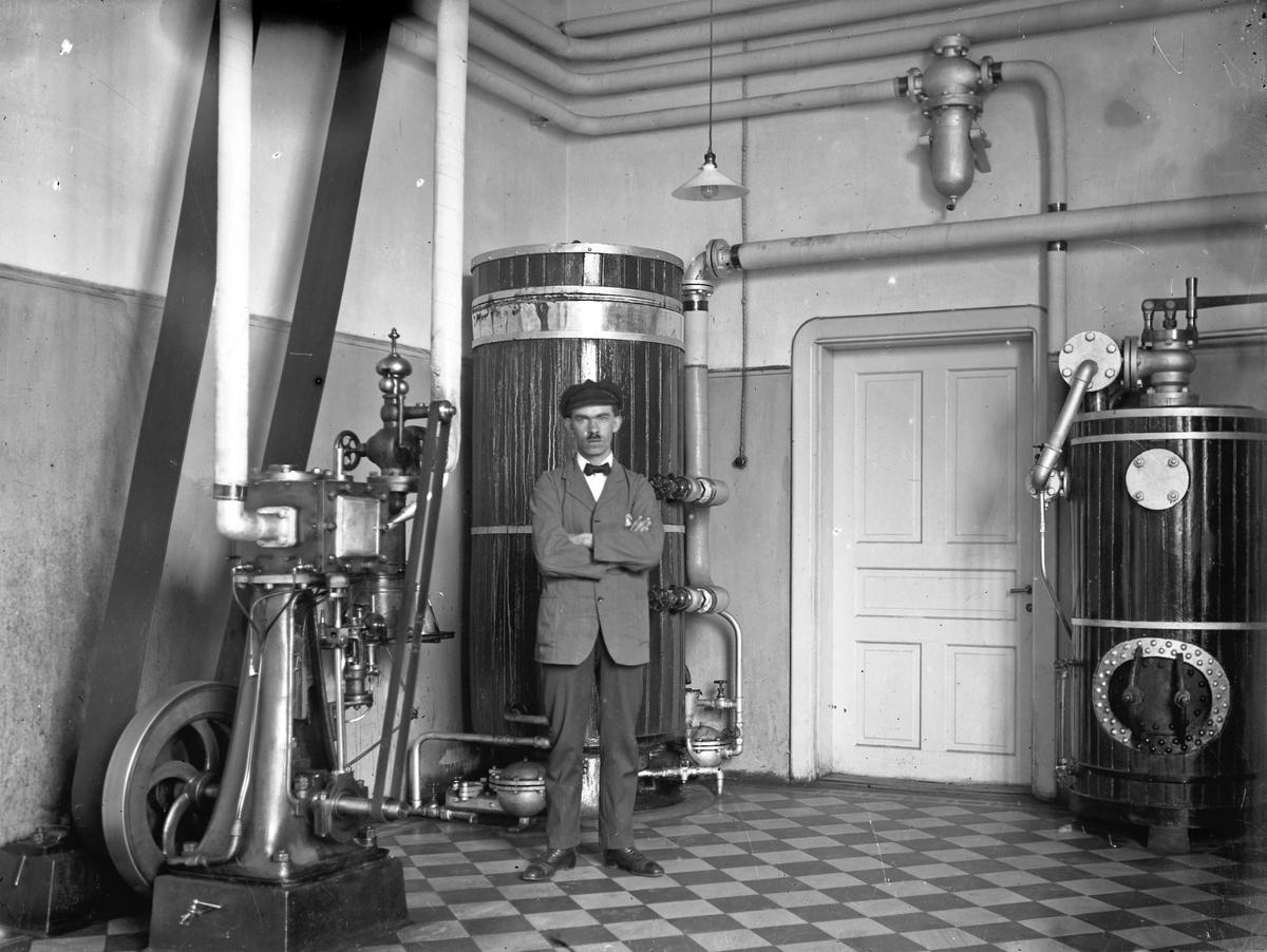 Man (okänd) som står i Alingsås lasaretts maskinhall.