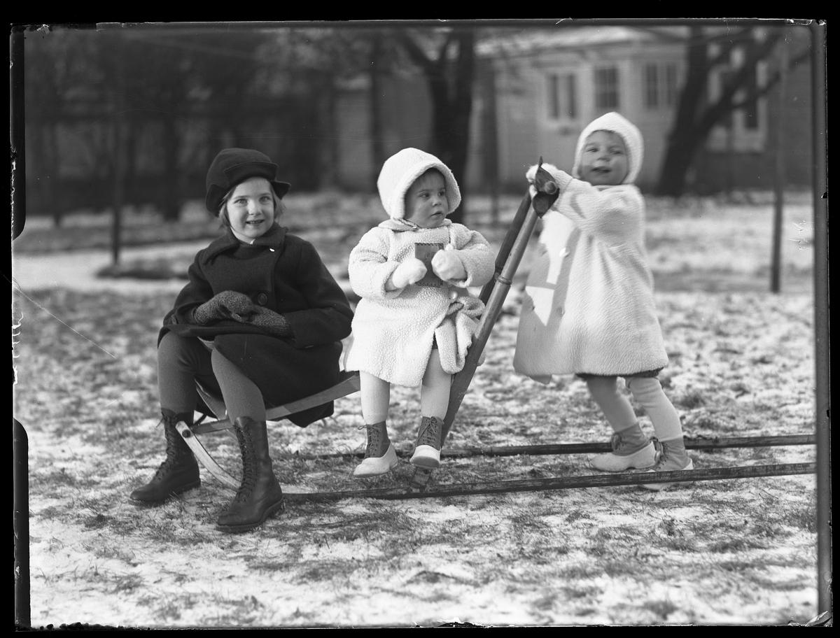 """Två barn sitter på en spark medan ett barn står bakom och håller i sparkens handtag. De två yngsta är tvillingar och är klädda i vita vinterkläder medan deras äldre syster är klädd i svart. I fotografens egna anteckningar står det """"Ing.[enjör] Bergs barn"""", tolkat som tvillingarna Peter Wilhelm och Ulla Maria samt deras syster Elsa Margareta."""