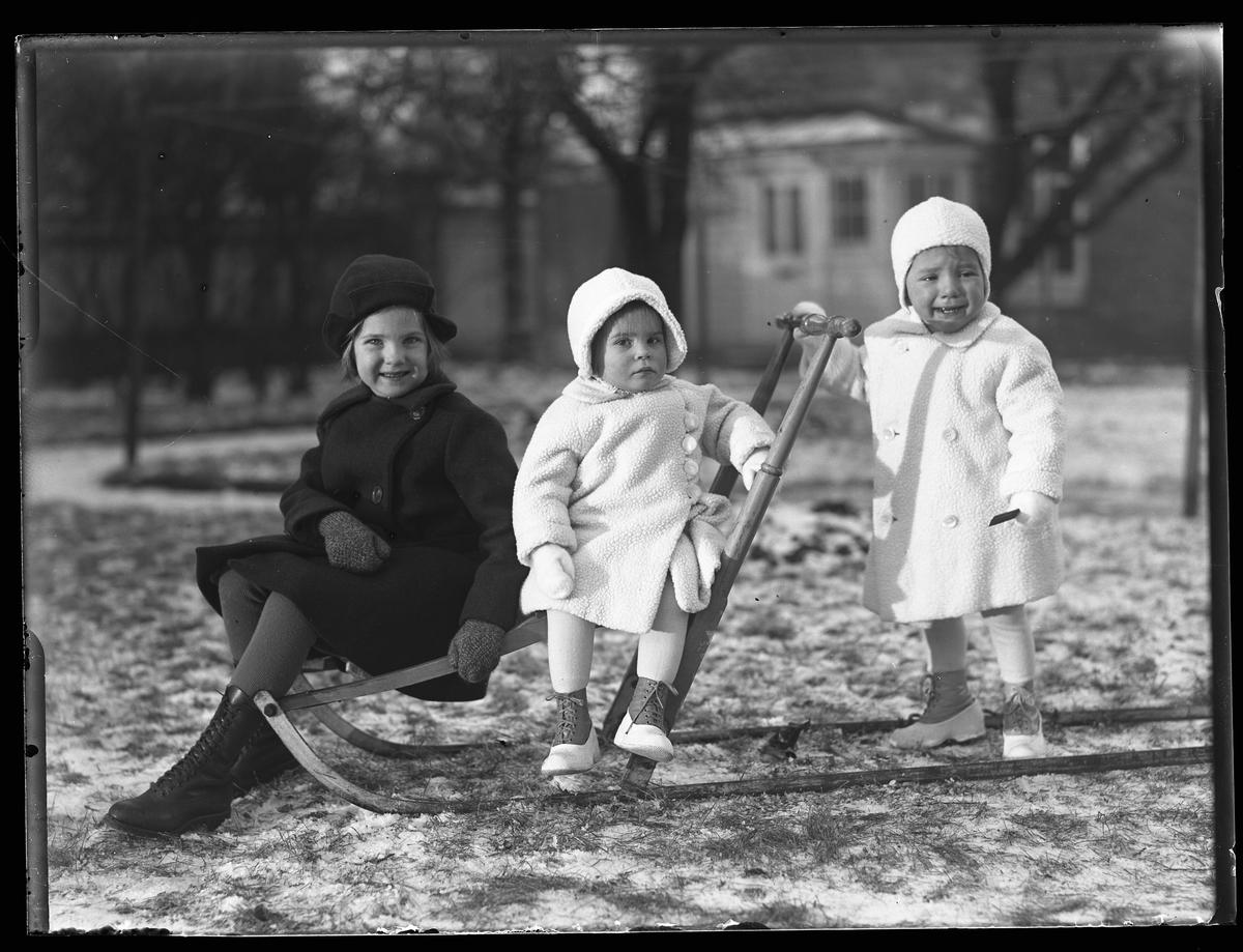 """Två barn sitter på en spark medan ett gråtande barn står bakom och håller i sparkens handtag. De två yngsta är tvillingar och är klädda i vita vinterkläder medan deras äldre syster är klädd i svart. I fotografens egna anteckningar står det """"Ing.[enjör] Bergs barn"""", tolkat som tvillingarna Peter Wilhelm och Ulla Maria samt deras syster Elsa Margareta."""