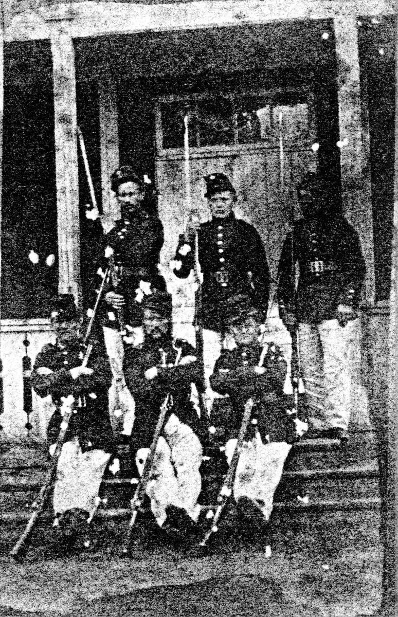 Gruppbild av 6 män i uniform med gevär, tillhörande Alingsås Skarpskyttekår. Stående till vänster August Bruno.